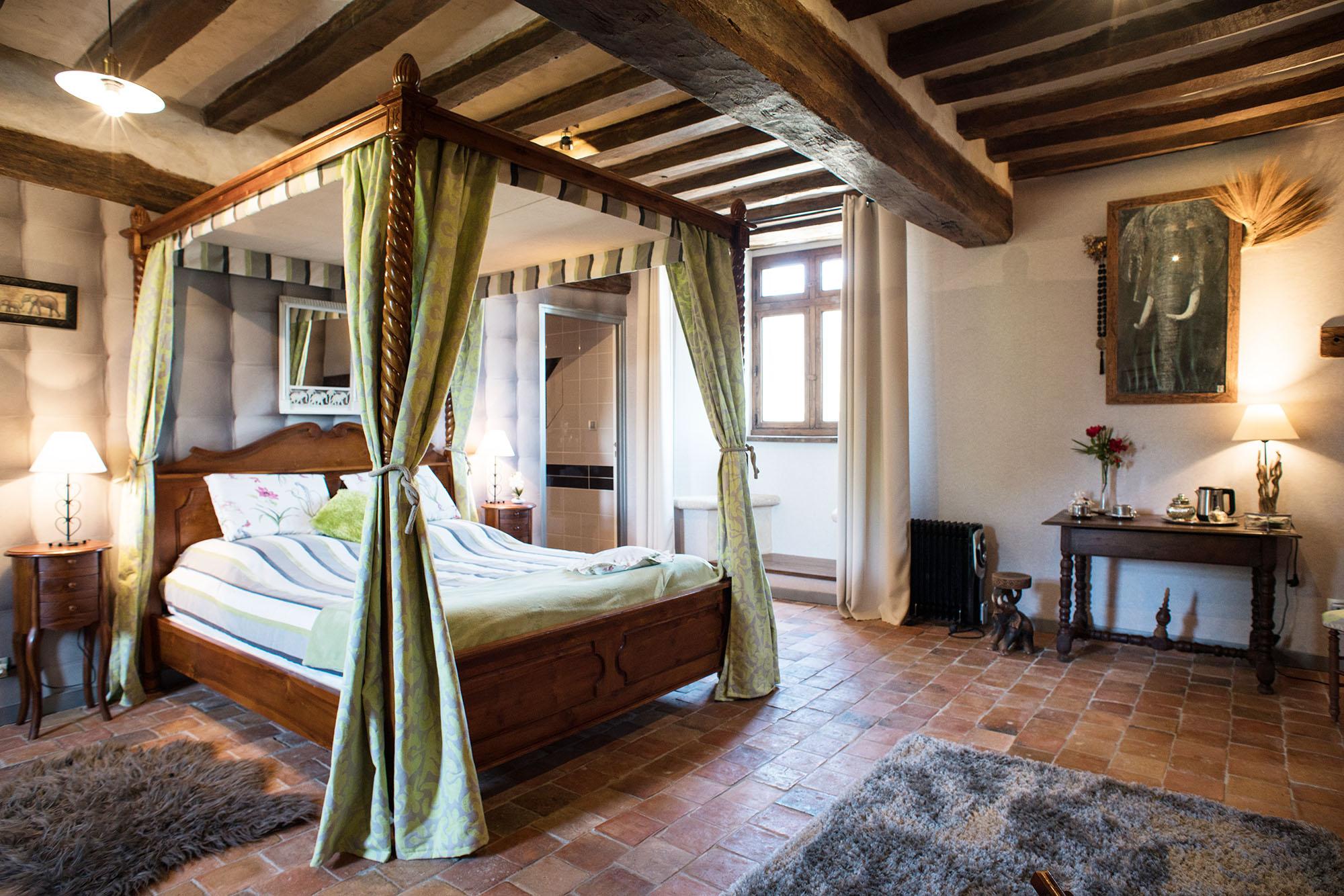 Chambre spacieuse avec lit traditionnel à baldaquin et poutres en bois au plafond.
