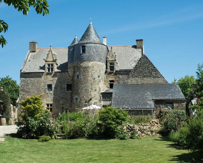 Façade de type médiéval avec jardin tout autour.