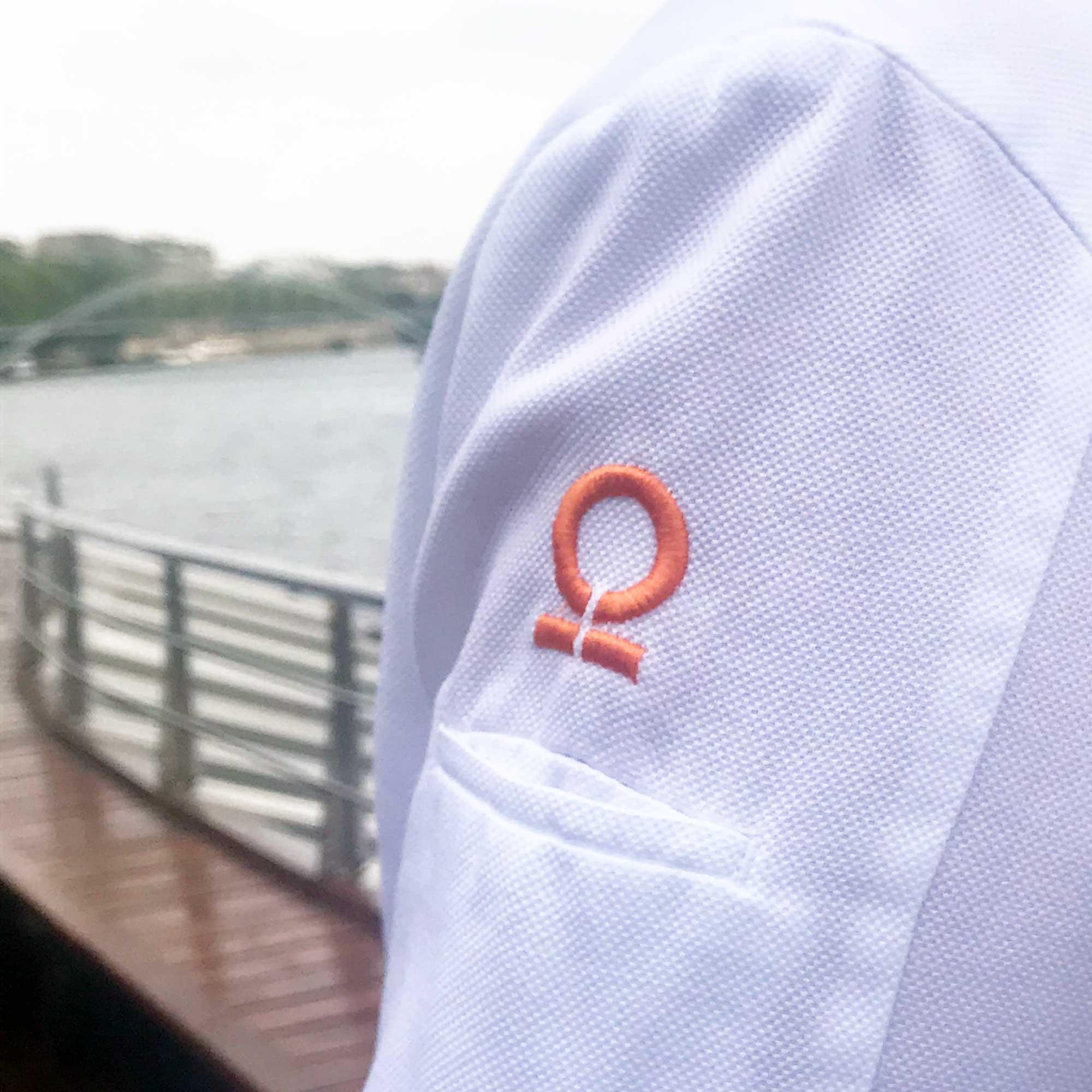 Épaule d'une veste de cuisiniers blanche avec un logo oméga orange