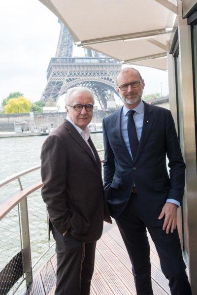Photo de deux hommes en costume à bord d'une péniche, arrière-plan Tour Eiffel