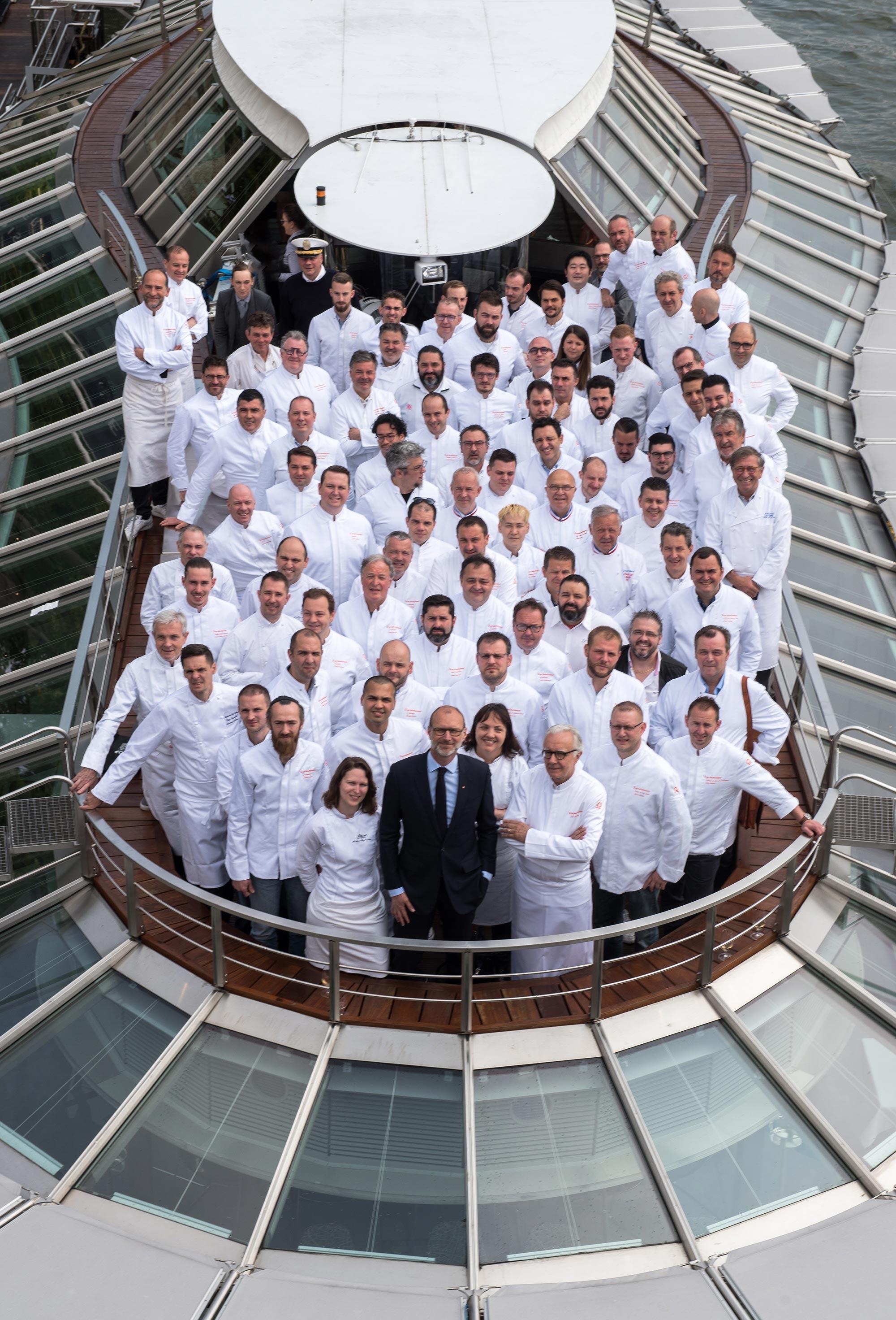 Photo collégiale de plusieurs chefs en veste de cuisinier blanche, réunis sur une péniche