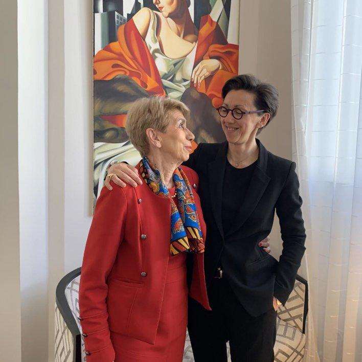 Deux femmes, une vêtue de rouge à gauche et l'autre vêtue de noir à droite, dans les bras l'une de l'autre, épaule contre épaule