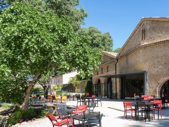 cour intérieure d'une bâtisse typique provençale avec une terrasse et quelques mobilier de jardin en rouge et noir