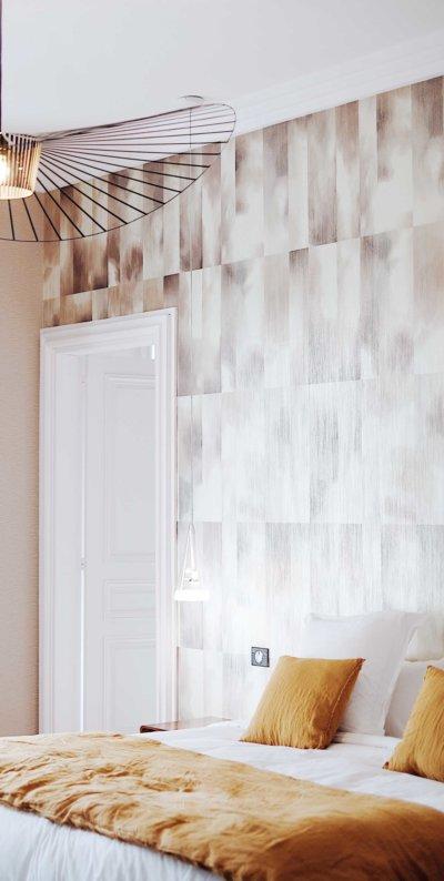 Détail de chambre avec lit couleur daim, papier peint graphique et suspension moderne en fil de fer noir