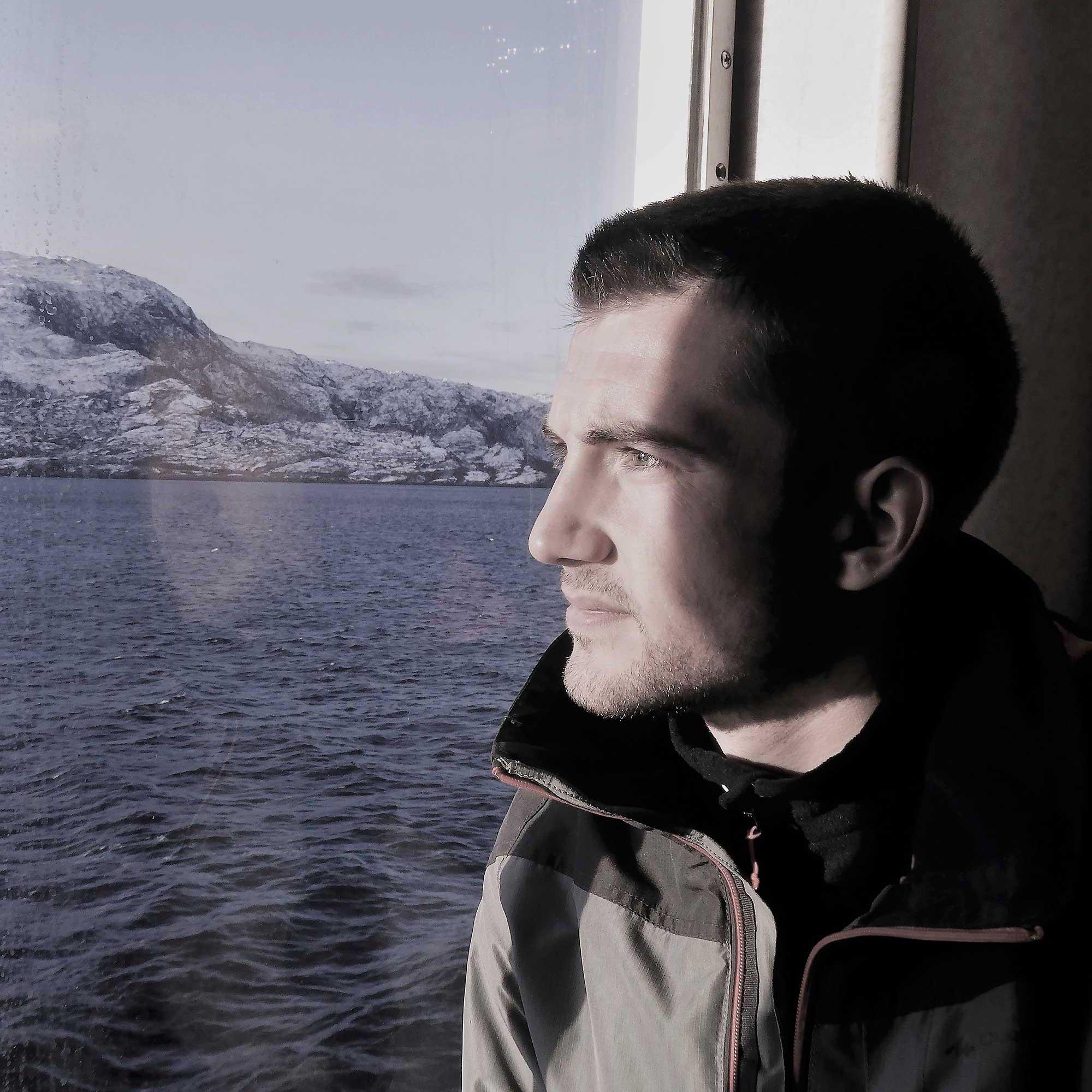 Photo portrait d'un homme de profil dans une cabine de bateau le regard contre la vitre