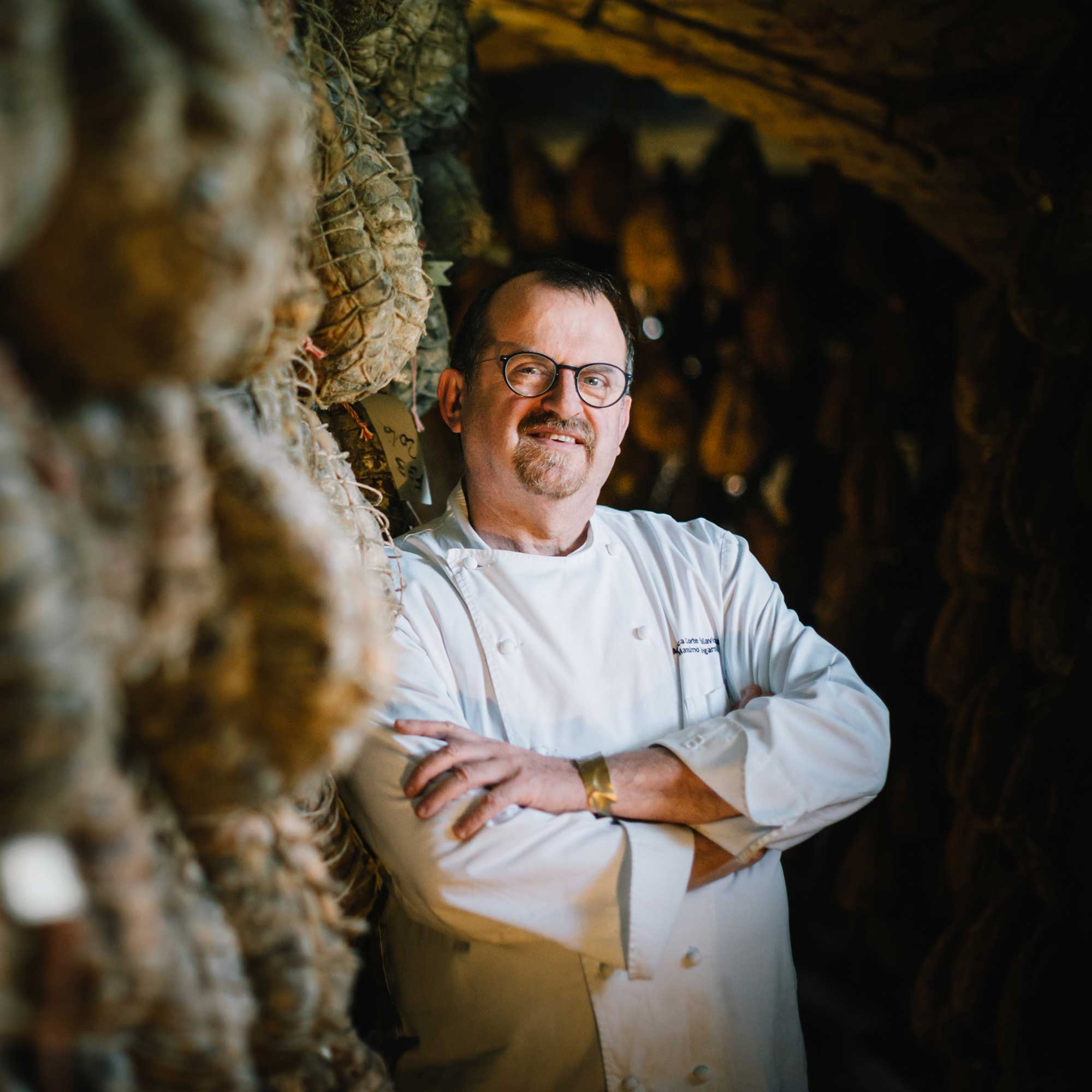 Photo portrait d'un chef en veste blanche, il pose devant des Culatello di Zibello, un jambon italien