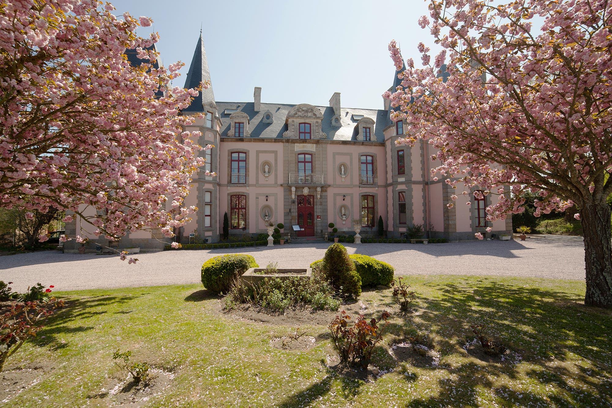 Façade traditionnelle en pierre d'un château avec des tourelles, agrémenté d'un jardin devant planté d'arbres à fleurs roses.