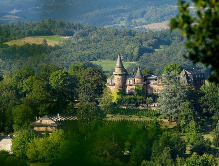 Château pris du haut d'une butte au cœur d'une vallée arborée