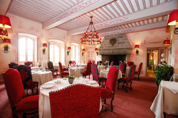 Salle de restaurant typique d'un château avec chaise capitonnée rouge et table nappée blanc