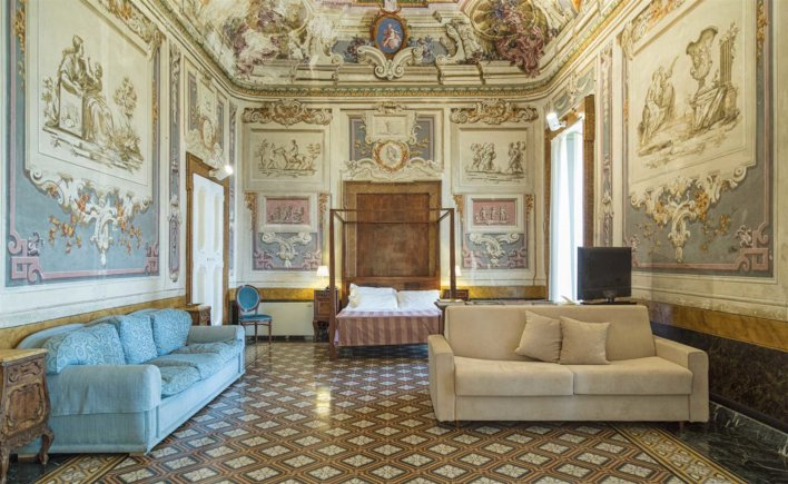 Chambre suite avec lit double, deux canapé, importante hauteur sous plafond et peinture aux murs