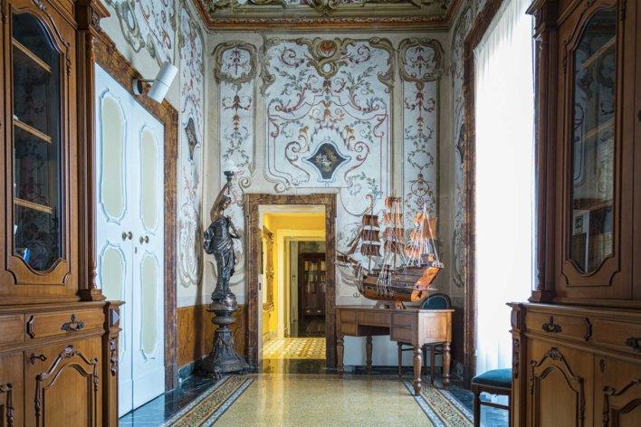 Couloir décor italien avec meubles en bois et maquette d'un trois mats