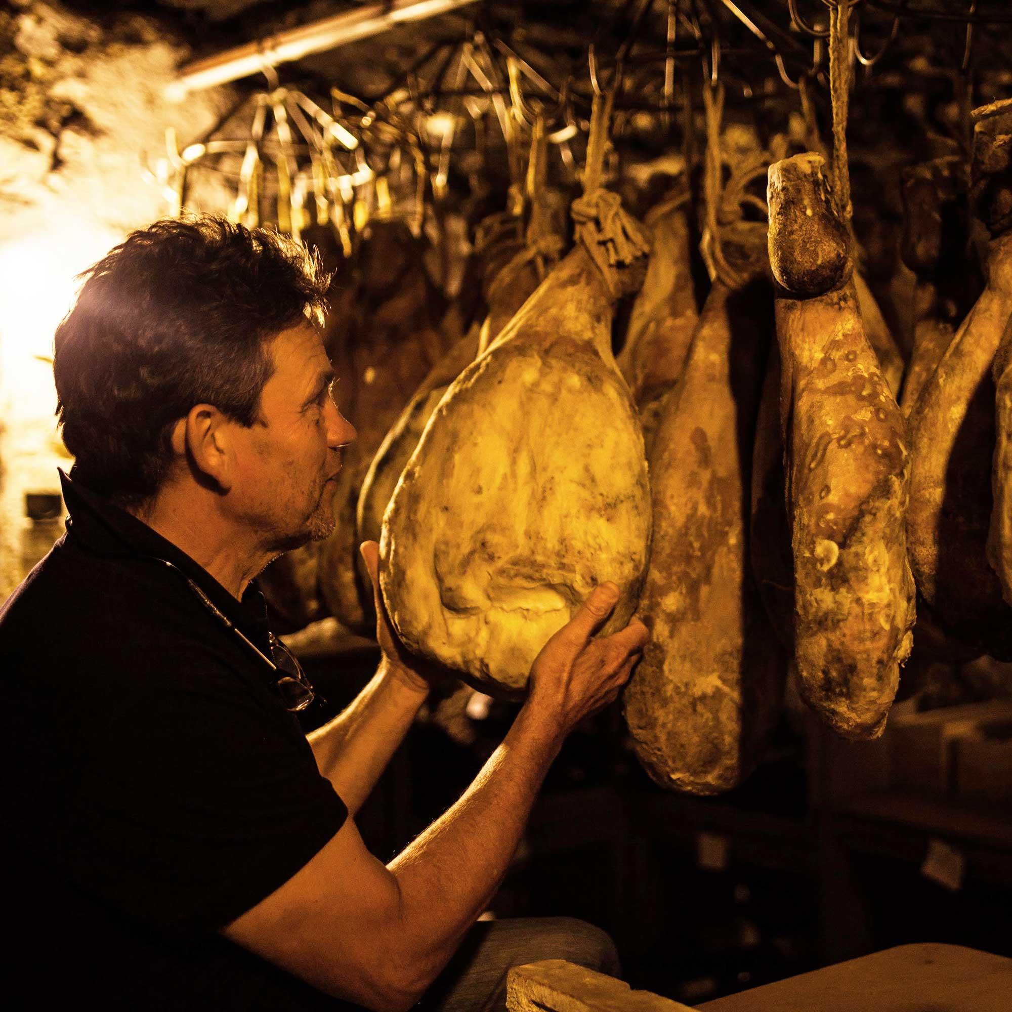 Homme en t-shirt noir dans une cave d'affinage de jambon, il tient un jambon dans les main
