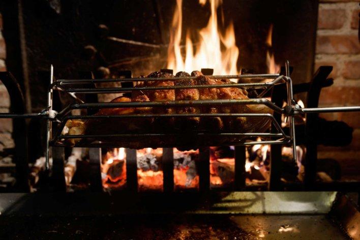 Pièce de viande à la broche qui tourne devant une cheminée au feu de bois