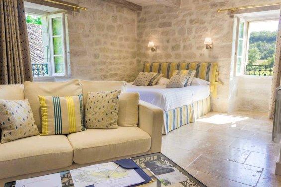 Chambre avec pierre apparentes, lit double et porte ouverte sur l'extérieur