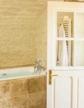 Salle de bain avec revêtement de baignoire en pierre et porte ouverte sur l'extérieur