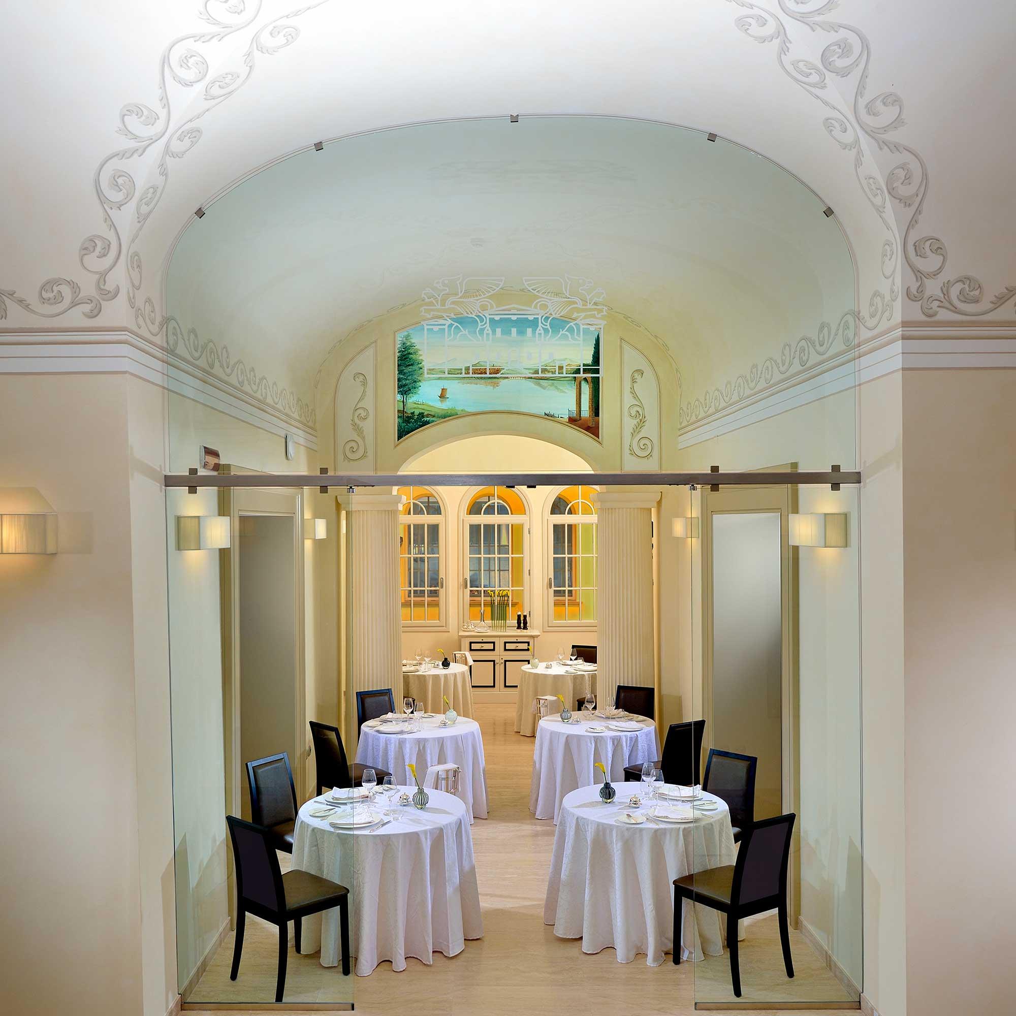 Salle de restaurant sous alcôves avec tables nappées blanches