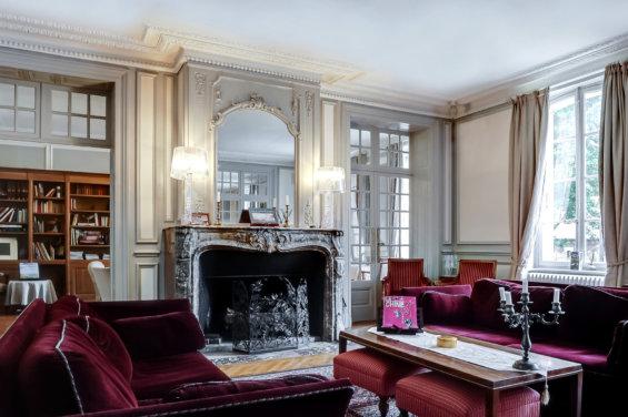 Salon avec cheminée, miroir et canapé.