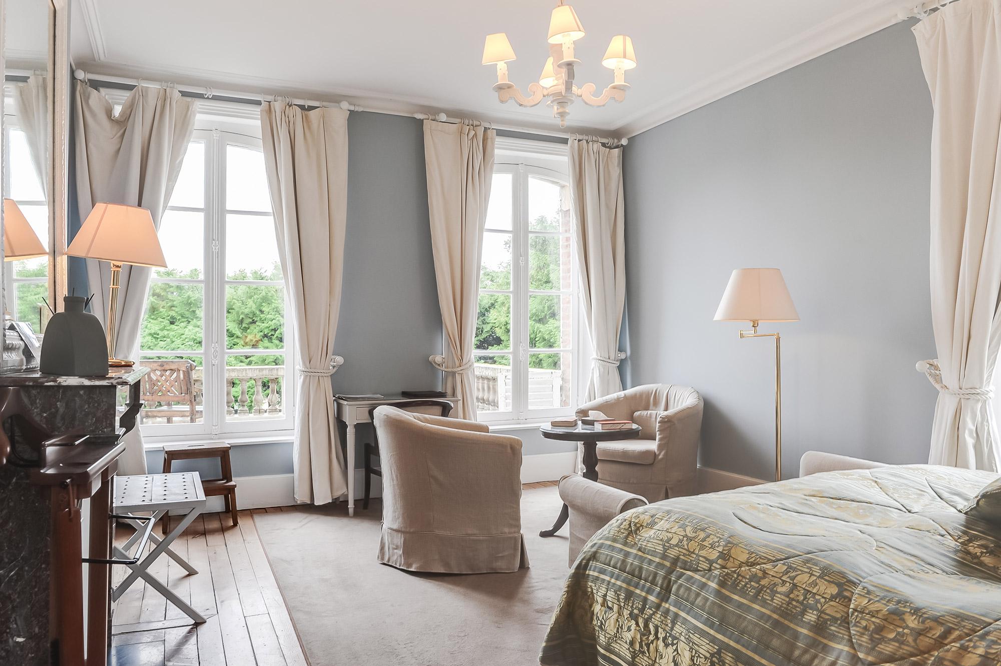 Chambre d'hôtel avec lit double et petit salon.