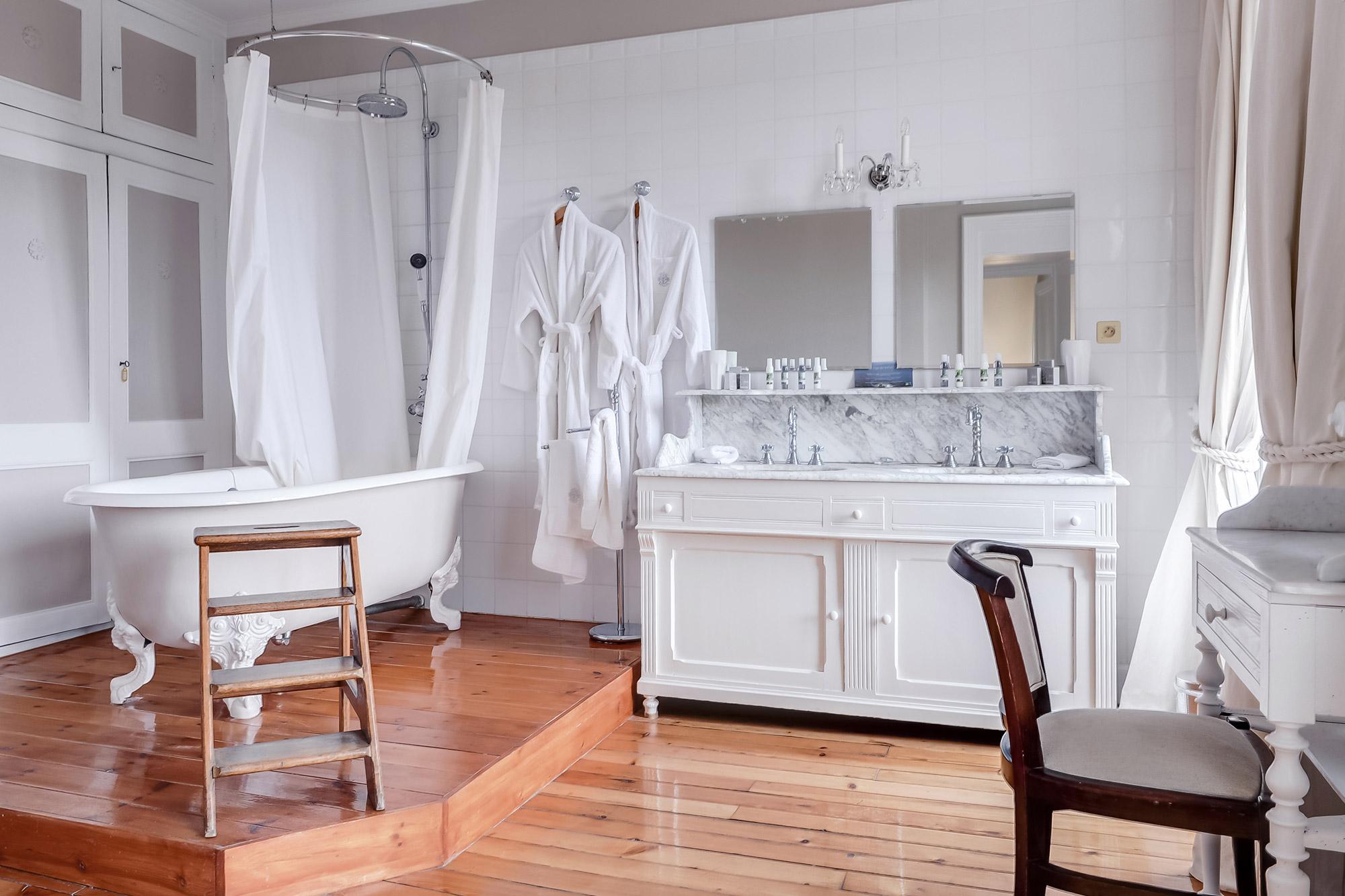 Grande salle de bain avec parquet au sol et baignoire vintage à pattes de lion.