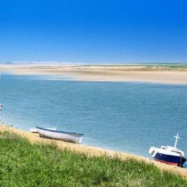 Paysage côtier du nord de la France avec petits bateaux acostés sur le sable.