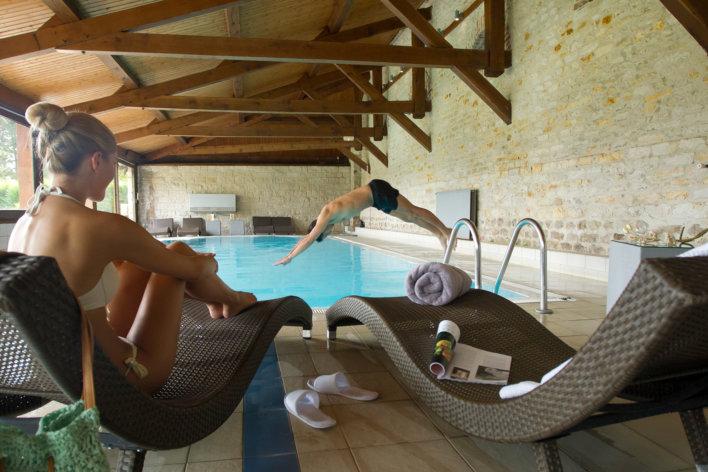 Jeune femme assise sur un transat pendant qu'un jeune homme effectue un plongeon dans la piscine.
