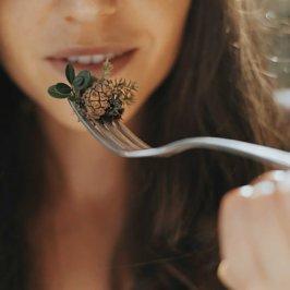Close-up sur une fourchette avec petite pomme de pain et femme en arrière plan