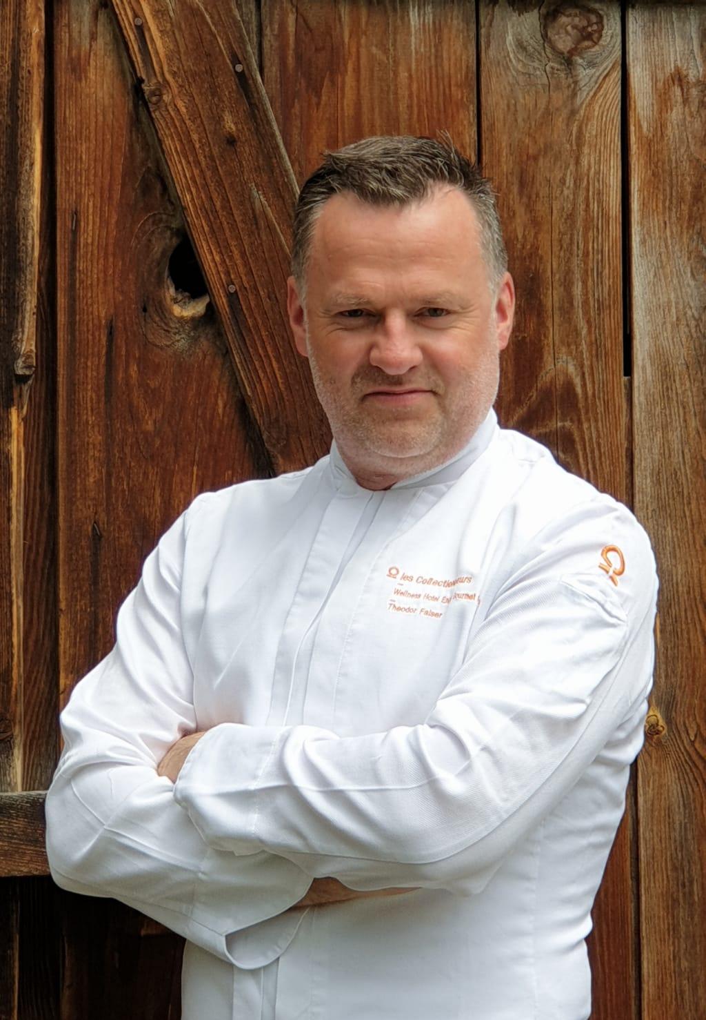 portrait de chef en veste blanche devant une porte en bois