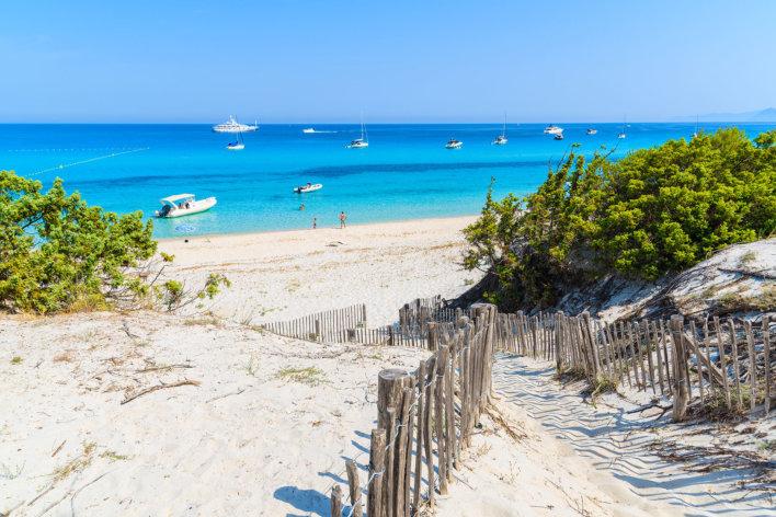 Accès à une place de sable blanc avec ciel bleu azur en Corse.