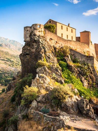 Vue en contre-plongée d'une citadelle nichée sur une falaise.