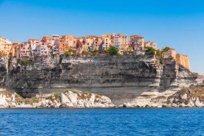 Succession de maisons aux couleurs chaudes construites sur de hautes falaises.