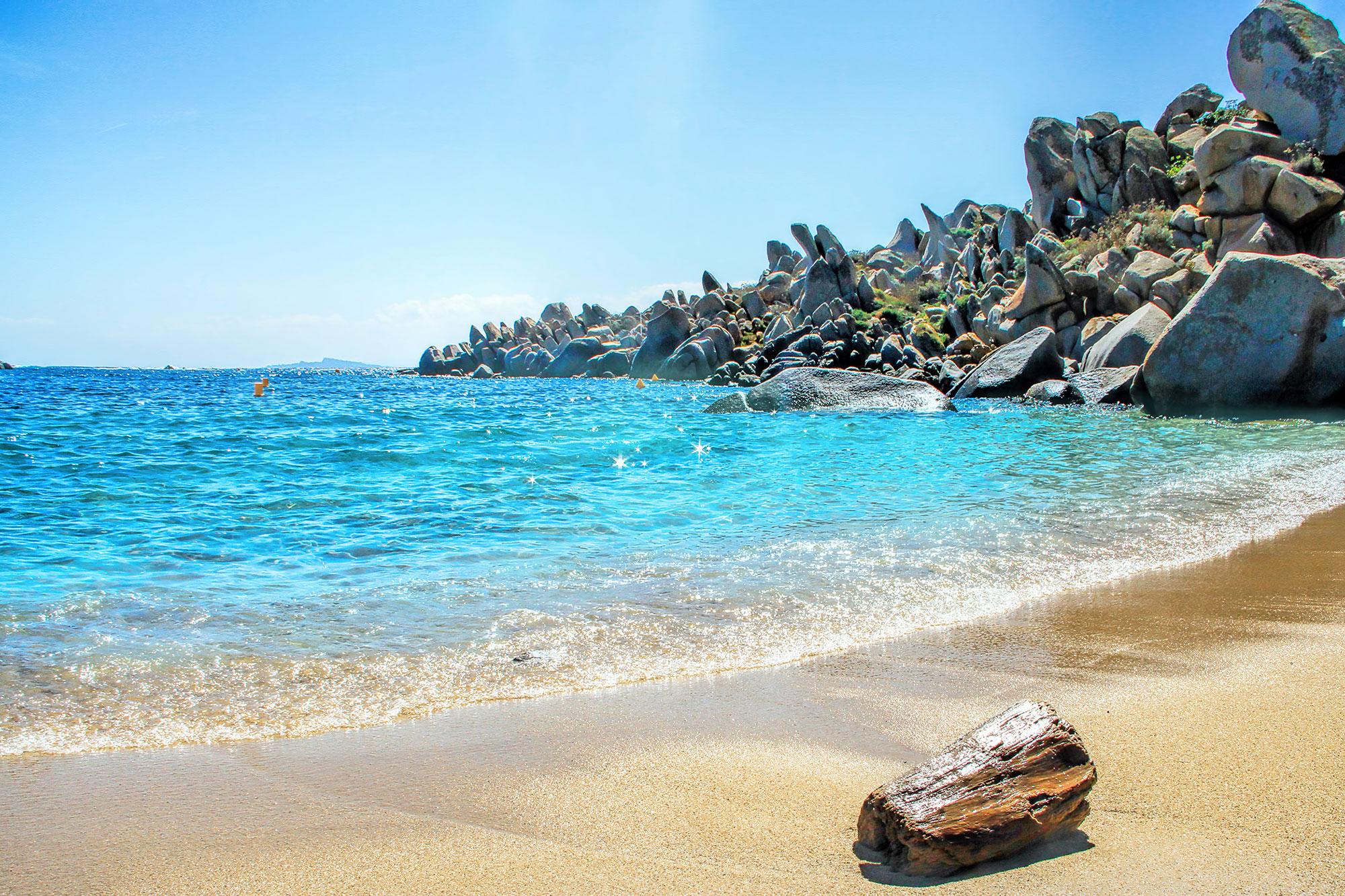 Plage de sable doré avec mer turquoise.