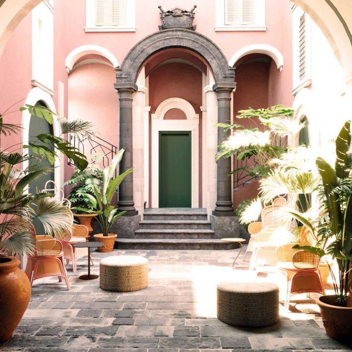 Cours intérieur d'un hôtel au style architectural sicilien, ton de rose, de vert et mobilier en paille et tressage