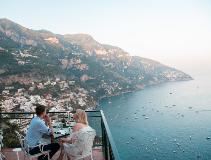 Couples d'une femme à gauche et d'un homme à droite, attablée avec une vue sur la mer