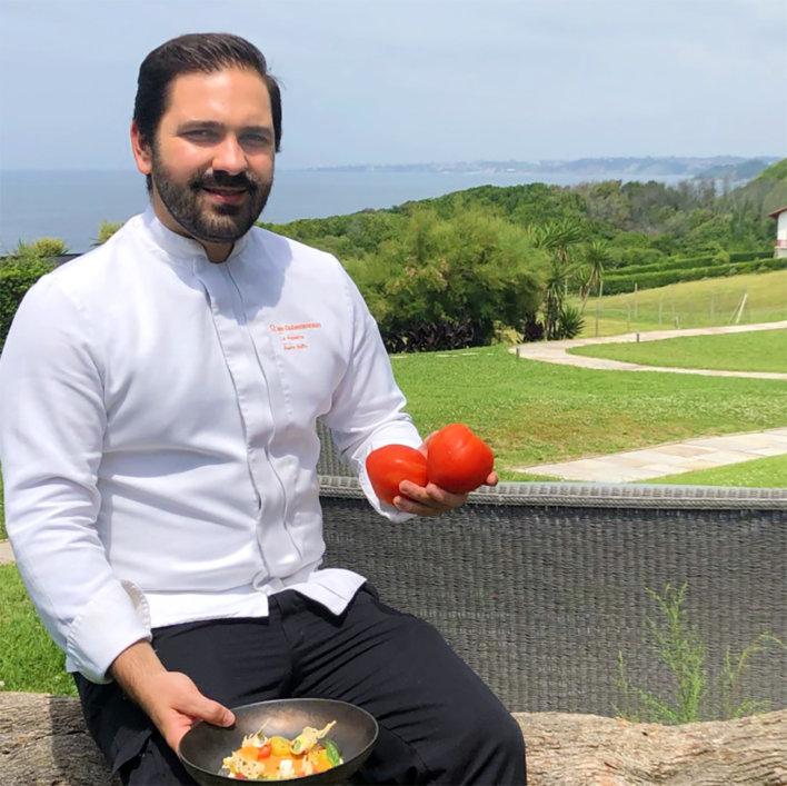 Chef en veste blanche tenant deux tomates rouges dans la main droite et une assiette dressée dans la main gauche, il est assis sur un muret avec vue mer