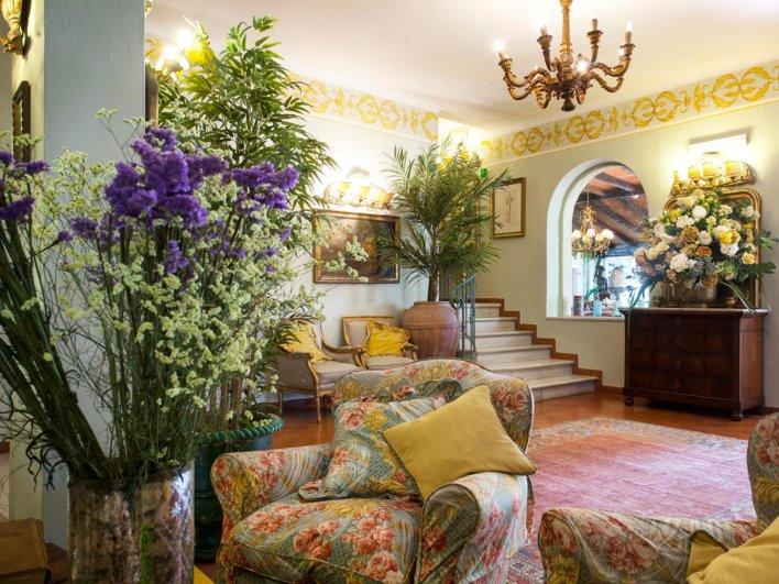 Hall d'entrée d'un hôtel dans une décoration à l'italienne, moulure, dorure et grand tapis rouge au sol, quelques vases avec fleurs
