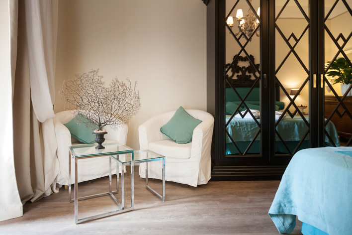Détail salon avec deux fauteuils en lin beige, table basse gigogne et porte vitrée avec détail fer forgé