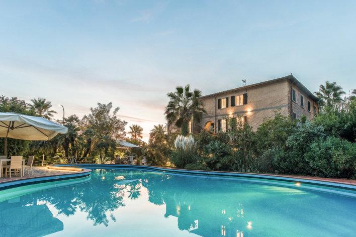 Piscine avec vue sur villa typique italienne et végétation tropicale