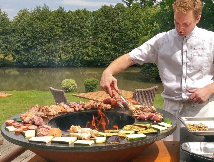 Chef en veste de cuisinier autour d'un brasero