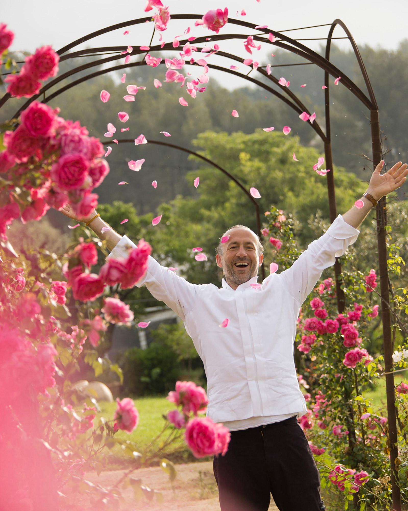 Chef en veste blanche dans un jardin jetant des pétales de rose en l'air