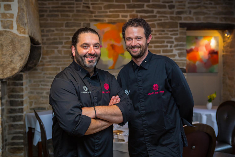 Deux chefs en veste noire de cuisinier au milieu d'une salle de restaurant