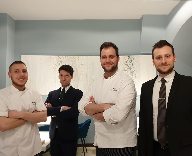 Quatre chefs et sommeliers réunis dans la salle d'un restaurant