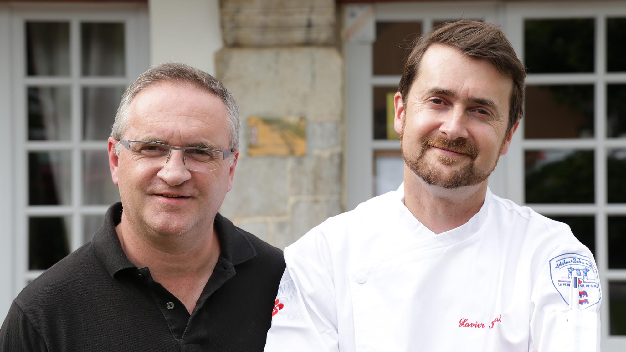 Deux hommes l'un à côté de l'autre, le premier en polo noir, le second en veste de cuisinier
