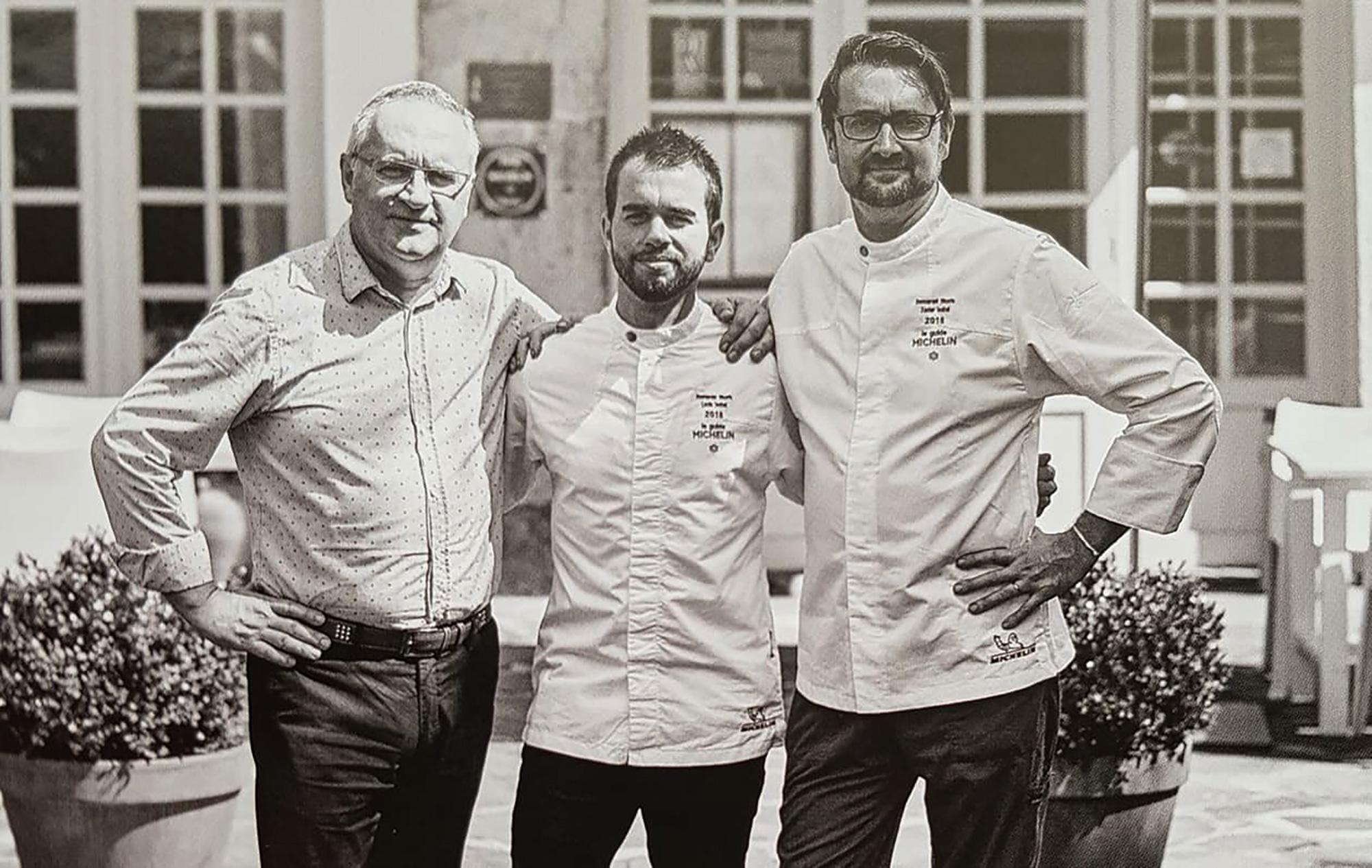 Photo noir et blanc de trois hommes se tenant épaule contre épaule