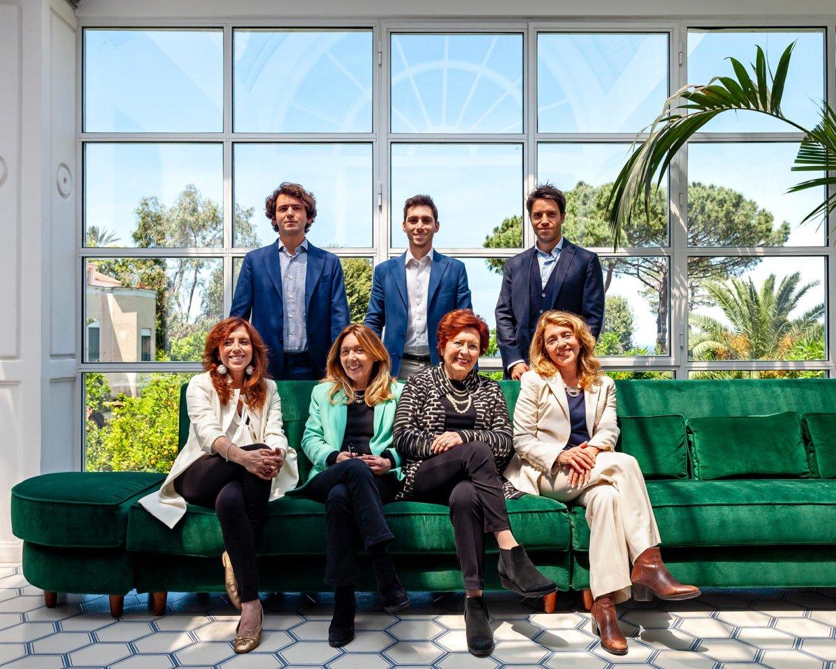 Photo de famille avec sept personnes, quatre femmes assises et trois hommes derrières debout