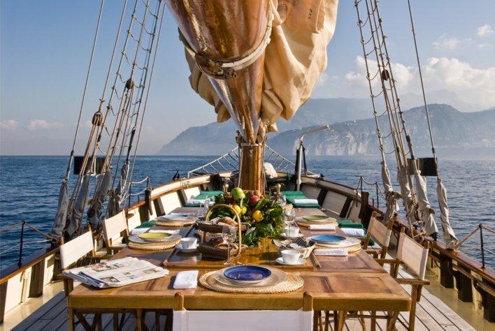 Table dressée pour cinq personnes sur un bateau avec un mat au centre de la table