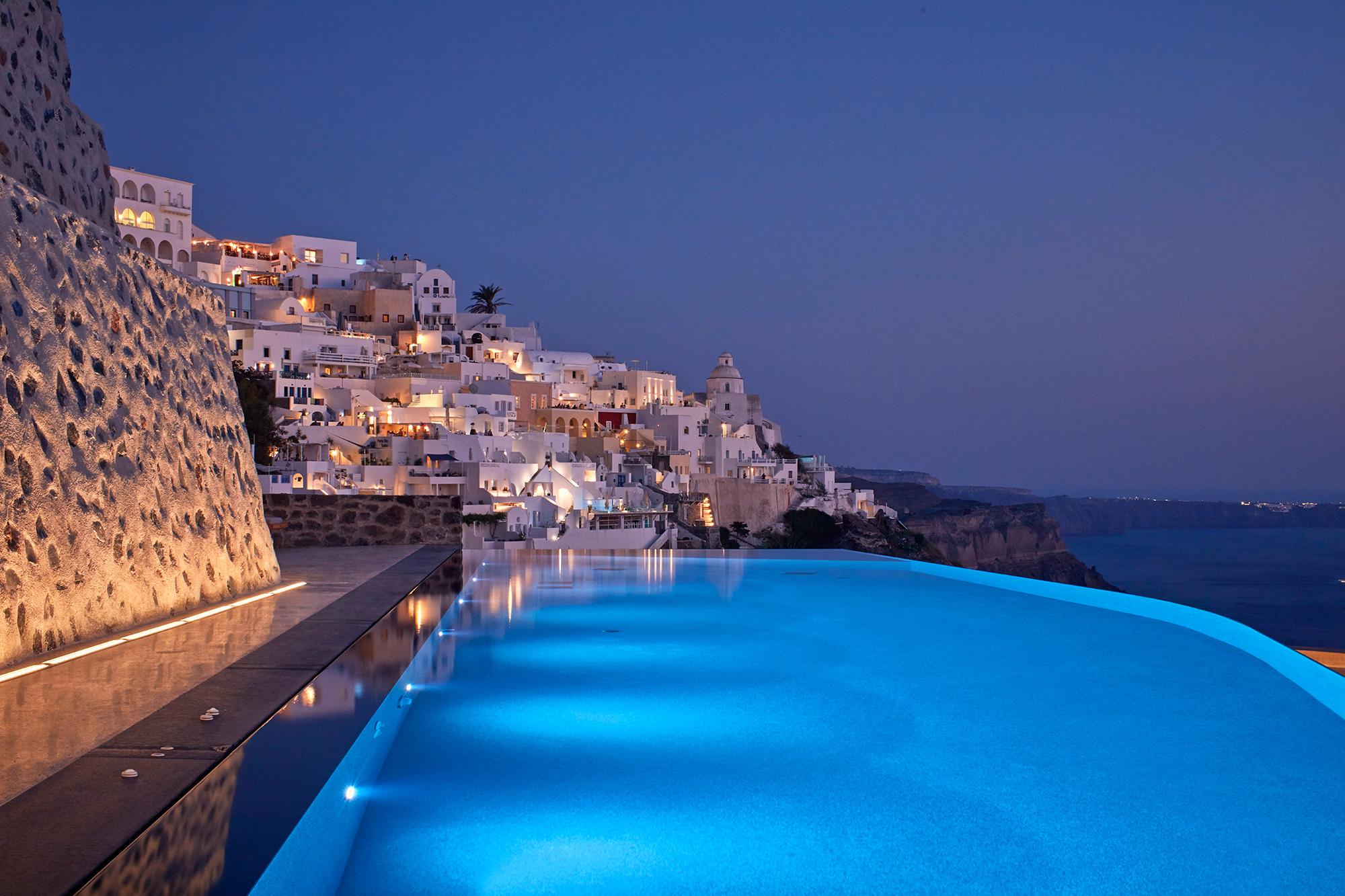 Piscine à débordement avec vue mer et colline avec maison en chaut blanche