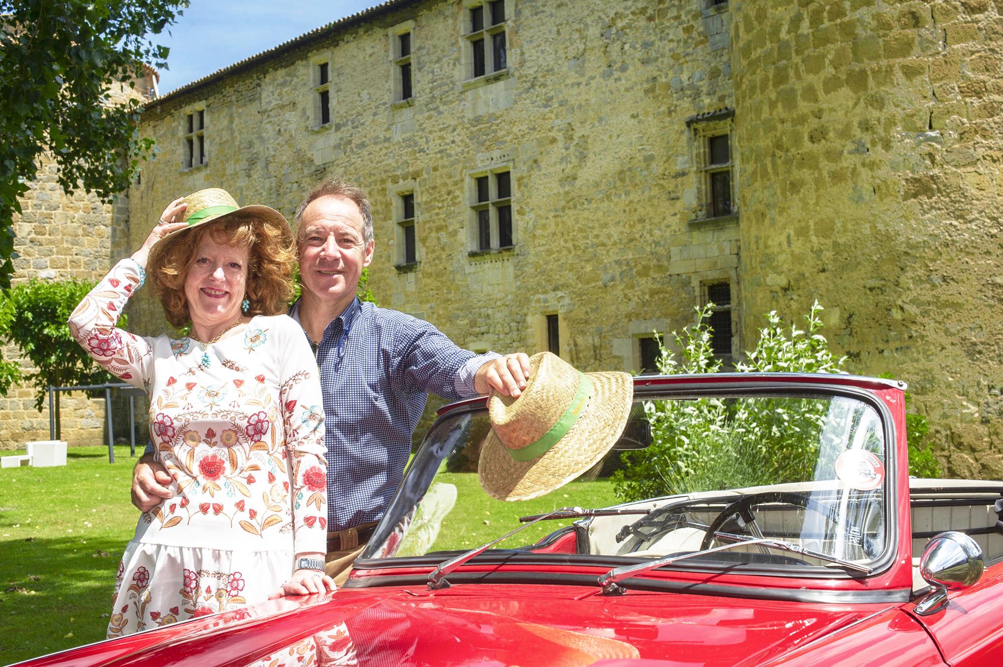 Une femme et un homme devant une voiture rouge avec un château en arrière-plan