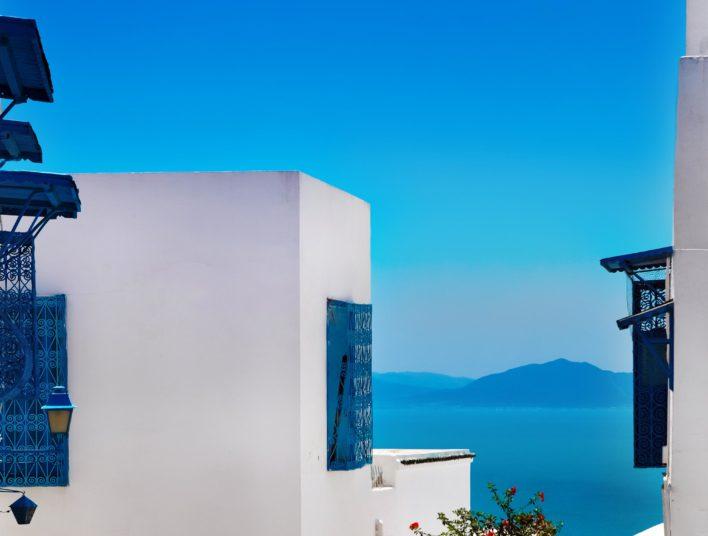 Ruelle typique de tunise avec maison en mur blanc et détails de boiseries et ferronneries bleus