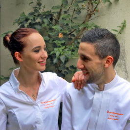 Deux chefs, une femme à gauche et un homme à droite en veste de cuisinier blanche brodée orange