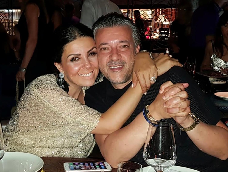 Une femme et un homme dans les bras l'un de l'autre sur attablés à une table de restaurant avec verre à vin